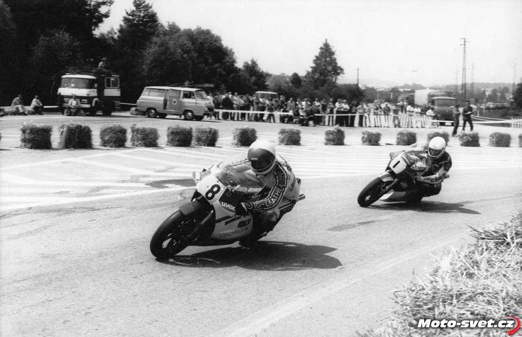 Zatáčka před cílem na křižovatce, kde je v současnosti druhý kruhový objezd - větší ohavnost se jen tak nevidí... Na fotografii z roku 1984, jede v čele závodu 500 ccm: #8 Sepp Doppler (A)...